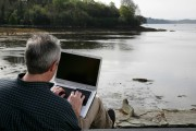 Man on computer in front of lake